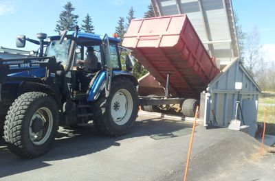 Tractor dumping woodchips into a prefabricated biomass heating plant